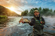 Quadro Sport fisherman holding trophy fish. Outdoor fishing in river