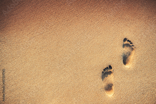 Footsteps on the beach over sand background