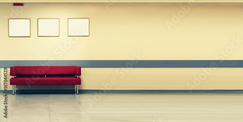 Style minimalism. Red Sofa, interior design, office. Empty waiting room with a modern red sofa in front of the door and three empty frames on the wall © gannamartysheva