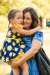 cute little girl hugging her mother outdoor shot in park