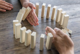 Hand stopping domino effect of wooden blocks for concept about business and accountability. - 167048516