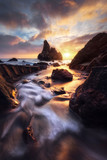 A stream feeds the ocean during a spectacular sunset at Sonoma Coast State Park.