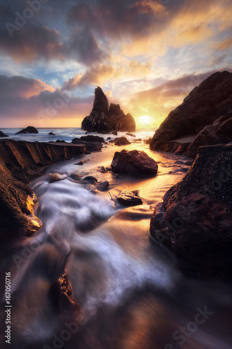 Fotobehang Zwart A stream feeds the ocean during a spectacular sunset at Sonoma Coast State Park.