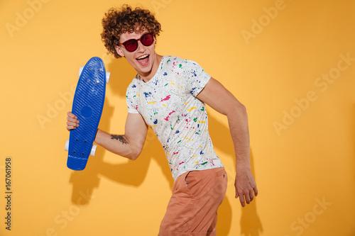 Foto op Aluminium Skateboard Happy cheerful guy in sunglasses walking