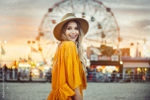 Poster Beautiful exited smiling tourist woman having fun at amusement park at hot summer day trip on the beach