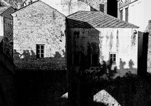 "Постер, картина, фотообои ""people silhouette on medieval stone house wall, Mostar, Bosnia and Herzegovina, black and white, concept"""