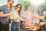 Couple standing and drinking alcohol at barbecue party