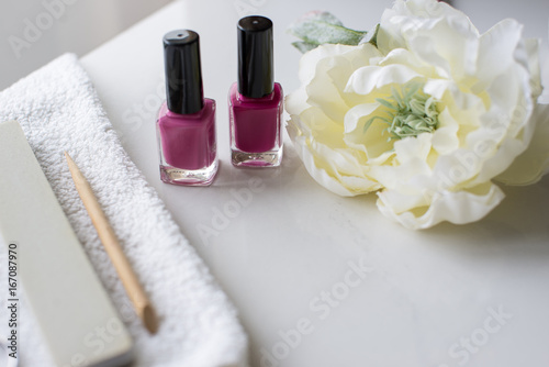 two pink polishes on the white manicure table