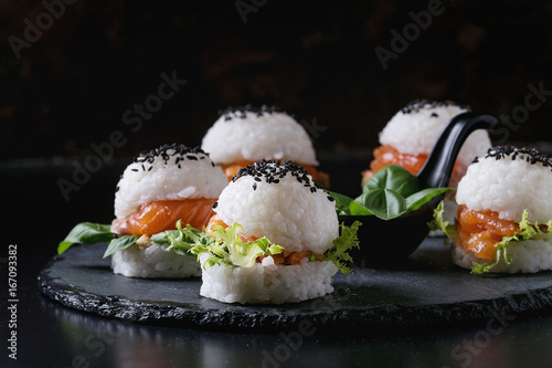 Papiers peints Sushi bar Mini rice sushi burgers with smoked salmon, green salad and sauces, black sesame served on slate stone board over black background. Modern healthy food