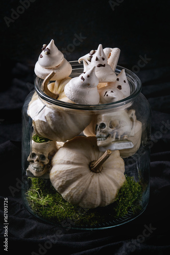 Halloween sweet dessert table decor glass jar with white meringue ghosts with chocolate eyes, decor skulls, moss and pumpkin over black background Poster