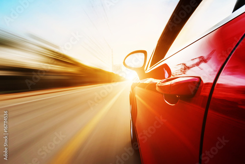 Fototapeta A car driving on a motorway at high speeds, overtaking other cars