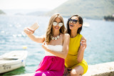 Two pretty young women taking selfie by the sea