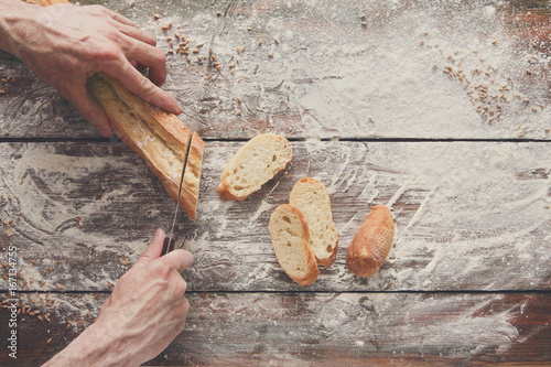 Bakery concept background. Hands cutting bread loaf slices
