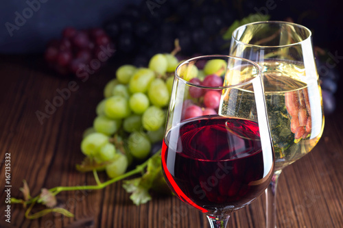 Leinwanddruck Bild Glasses with red and white wine with grapes on wooden background