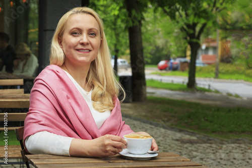 Smiling beautiful woman 45 years old drink coffee in a cafe. Poster