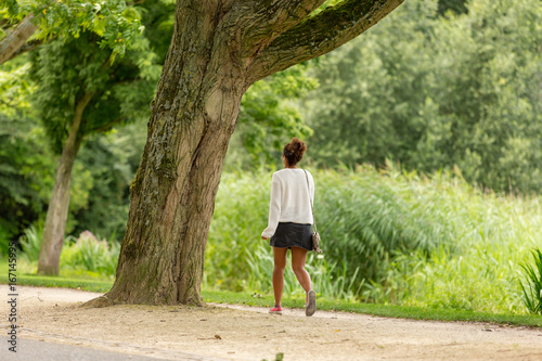 Papiers peints Nature A woman walking through the Amsterdam Vondelpark in the Netherlands.