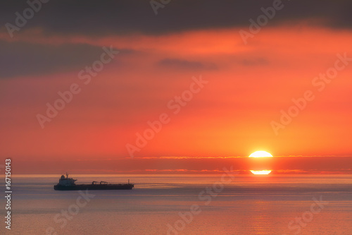 Deurstickers Koraal ship on the sea at sunset