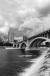 Cloudy morning in Minneapolis. Minneapolis downtown skyline and Third Avenue Bridge above Saint Anthony Falls and Mississippi river in black and white. Midwest USA, state of  Minnesota.