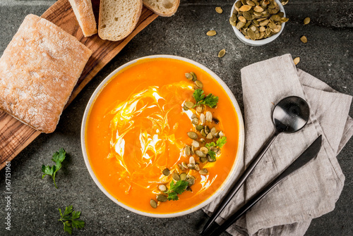 Traditional fall and winter dishes, hot and spicy pumpkin  soup with pumpkin seeds, cream and freshly baked baguette, on black stone table, copy space top view - 167151961
