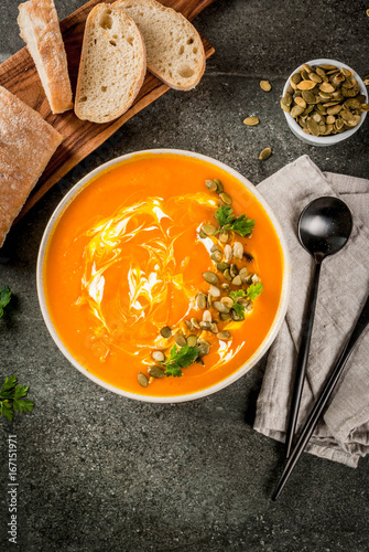 Traditional fall and winter dishes, hot and spicy pumpkin  soup with pumpkin seeds, cream and freshly baked baguette, on black stone table, copy space top view - 167151971