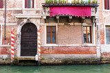 Small canal in venice with old buildings balconies a fading painted walls