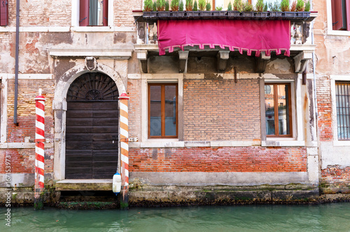 Foto op Canvas Venetie Small canal in venice with old buildings balconies a fading painted walls