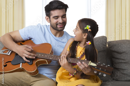 Father teaching daughter to play guitar