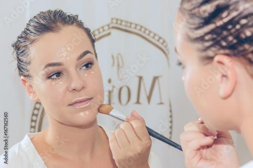 Leinwanddruck Bild Junge Frau im Spiegel schminkt sich