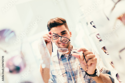 a582b3278d Handsome young man choosing eyeglasses frame in optical store.