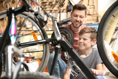 Deurstickers Dad and son fixing bicycle in garage