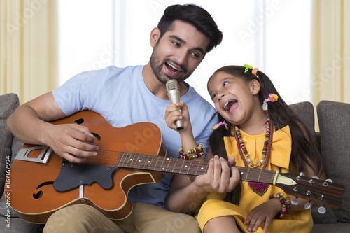 Father and daughter singing while playing guitar