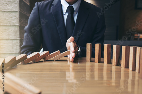 Close up of businessman hand Stopping Falling wooden Dominoes effect from continuous toppled or risk, strategy and successful intervention concept for business