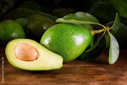 Ripe avocado on wooden table. Freshly harvested fruits