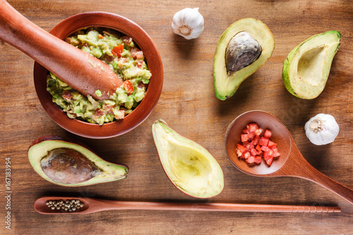 Top view of fresh homemade Guacamole in wooden mortar