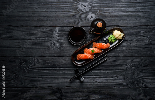 Japanese cuisine. Salmon sushi nigiri with soy sauce on a dark wooden background.