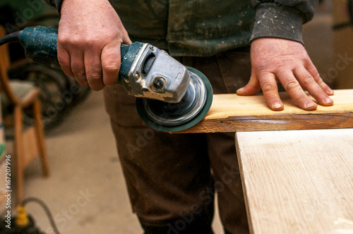 Wood sanding using grinders. Man in work clothes processing wood. - 167207996