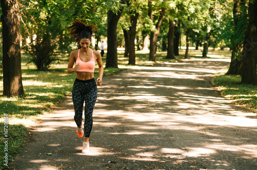 Poster Fit woman running outdoors in park on a sunny day