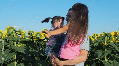 Happy family on the field of sunflowers. Father circles his daughters.