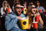 Laughing friends sitting in cinema watch film - 167259317