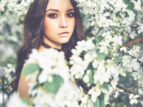Beautiful young woman surrounded by flowers of apple-tree - 167267589