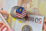 euro coin with national flag of malaysia on the euro money banknotes background.