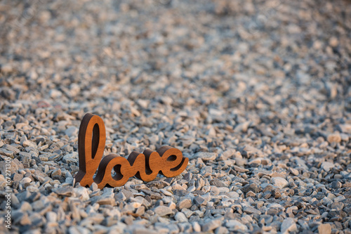 Wooden sign Love on the rocks, in the sunset