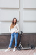 Beautiful young girl with long brown hair stopped while riding the scooter on the background of the gray wall. She is dressed in a white sweater and blue jeans