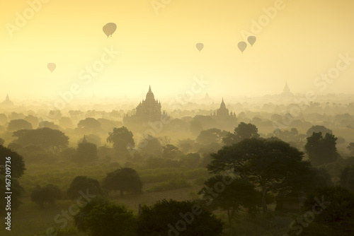 Hot air balloons fly over the pagoda ancient city field on silhouette sunrise scene at Bagan Myanmar.