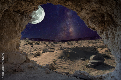 In de dag Nasa An unrealistic night landscape through a cave with milky, moon in eclipse, and desert with ruins of ancient columns.