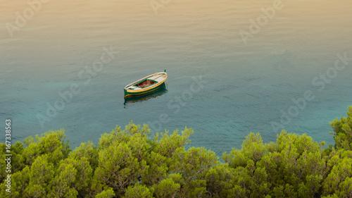 Small wooden boat on calm sea