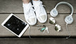 The concept of white color, headphones, tablet, glasses, sneakers and keys lie on a wooden surface. Office in the park