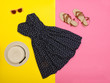 Fashionable concept. Female summer wardrobe. Straw hat, sundress, sunglasses, sandals. Yellow background, top view
