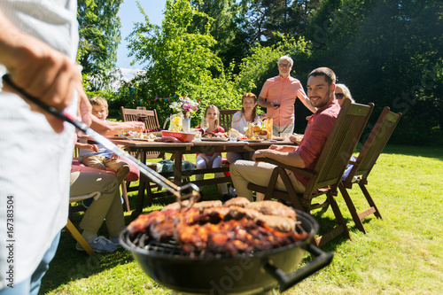 man cooking meat on barbecue grill at summer party - 167383504