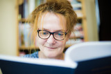 A smiling woman with glasses reads in a book - 167387354